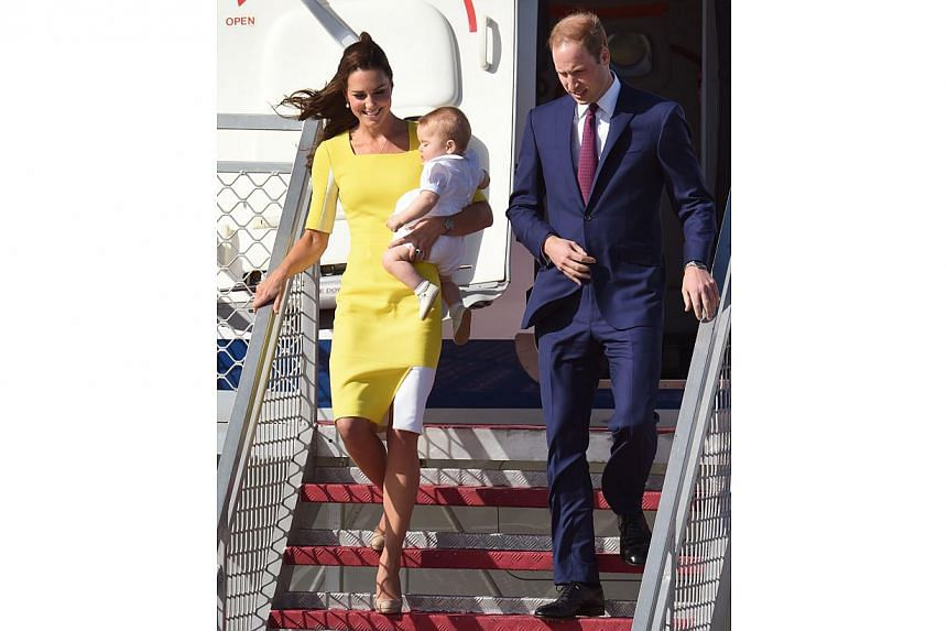 Britain's Prince William (right) and his wife Catherine, the Duchess of Cambridge, holding Prince George walk down the stairs upon their arrival from New Zealand at Sydney airport on April 16, 2014. -- PHOTO: AFP
