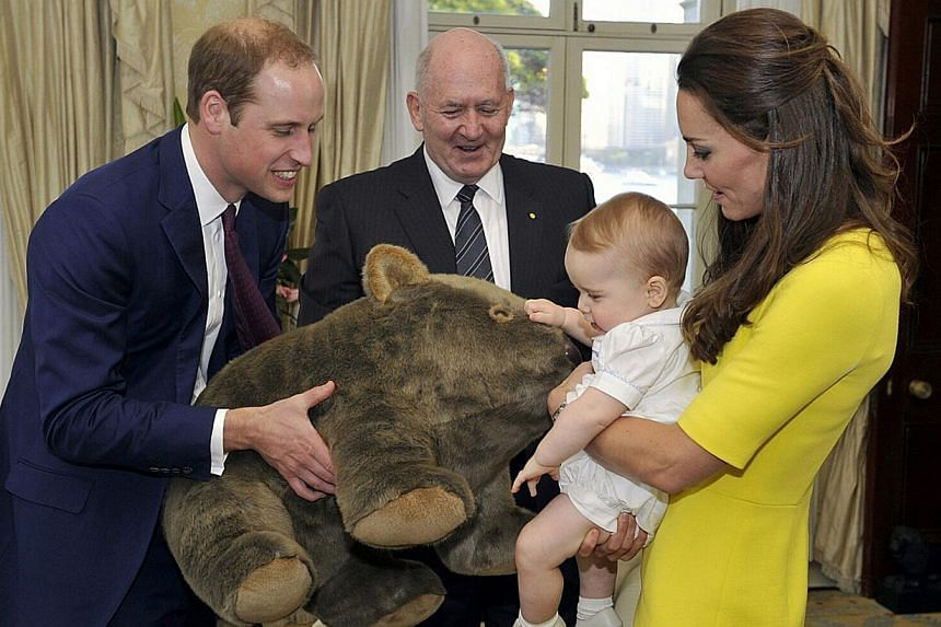 Catherine, the Duchess of Cambridge, holds her son Prince George as his father, Britain's Prince William (left), holds a toy wombat that was given as a present to him from Australia's Governor-General Peter Cosgrove (second, left) at Admiralty House