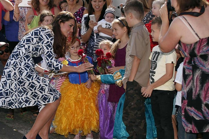 Catherine (left), Duchess of Cambridge, receives a flower from a girl as she meets locals during her visit to the Blue Mountains suburb of Winmalee, west of Sydney, with her husband, Britain's Prince William (not seen)on April 17, 2014. -- PHOTO: REU