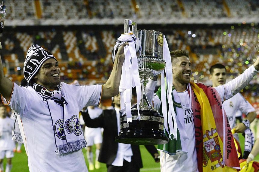 """Real Madrid's Portuguese defender Pepe (left) and defender Sergio Ramos hold the trophy after winning the Spanish Copa del Rey (King's Cup) final """"Clasico"""" football match FC Barcelona vs Real Madrid CF at the Mestalla stadium in Valencia on April 16,"""