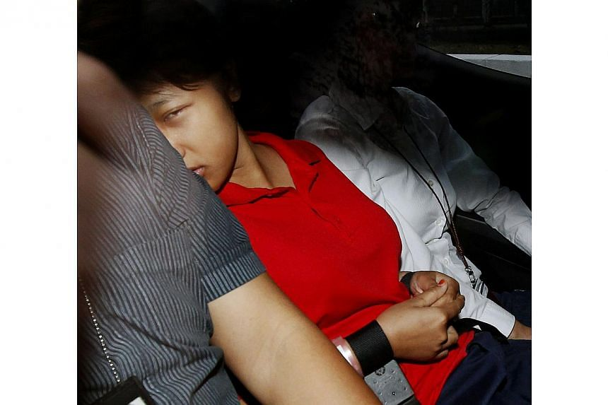 Indonesian maid Dewi Sukowati, wearing a red polo T-shirt, in a police car on March 20, 2014. -- ST FILE PHOTO: WONG KWAI CHOW