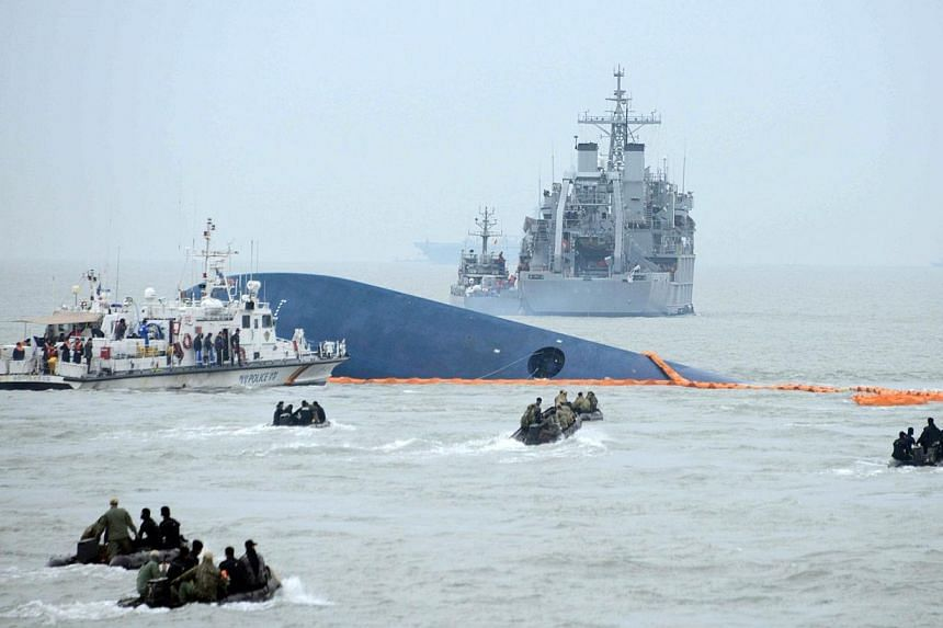 Coast guard members search for passengers near a South Korean ferry (centre) that capsized on its way to Jeju island from Incheon, at sea some 20km off the island of Byungpoong in Jindo on April 17, 2014.-- PHOTO: AFP