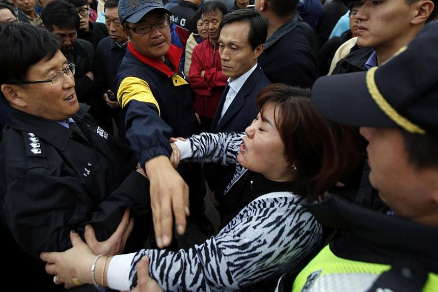 Family members of missing passengers on the South Korean ferry Sewol  jostle with coastguard and police officers as they demand the immediate restart of the search operation, at a port where family members of missing passengers have gathered in