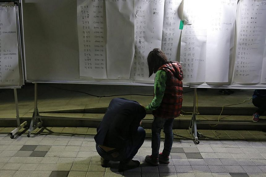 A family member of a missing passenger who was on the South Korean ferry Sewol ries after finding her son's name on the survivors list at a gym where rescued passengers gathered in Jindo on April 16, 2014.-- PHOTO: REUTERS