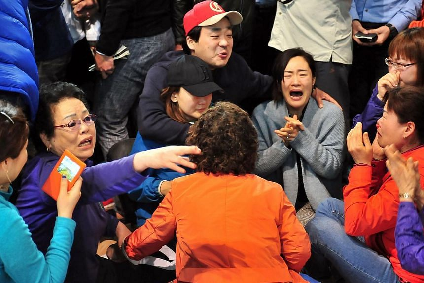 South Korean relatives of passengers on board a capsized ferry cry as they wait for news about their loved ones, at a gym in Jindo on April 17, 2014. -- PHOTO: AFP