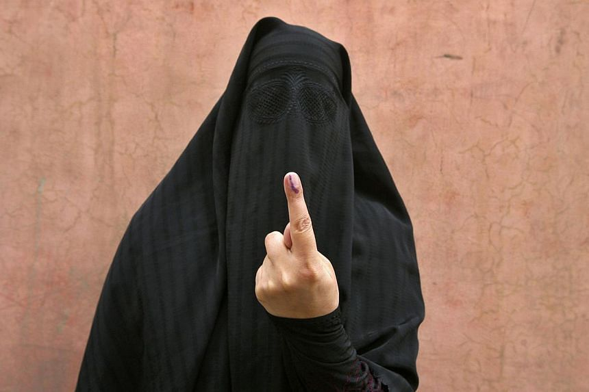 A veiled Muslim woman shows her ink-marked finger after voting outside a polling station in Doda district, north of Jammu, on April 17, 2014. Around 815 million people have registered to vote in the world's biggest election - a number exceeding the p