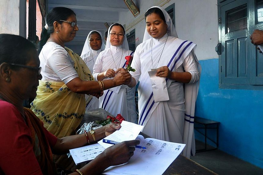 An Indian election official distributes red roses to Christian Nuns during voter registration in Ranchi on April 17, 2014, for national elections. -- PHOTO: AFP