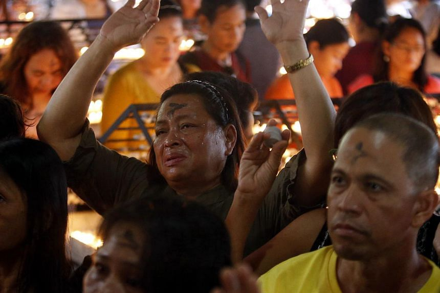 """Devotees pray during the commemoration of Ash Wednesday inside a Roman Catholic church in Paranaque, Metro Manila on March 5, 2014. Catholics in the country celebrated Ash Wednesday, which serves as a reminder that """"as a man is dust, so unto dust he"""
