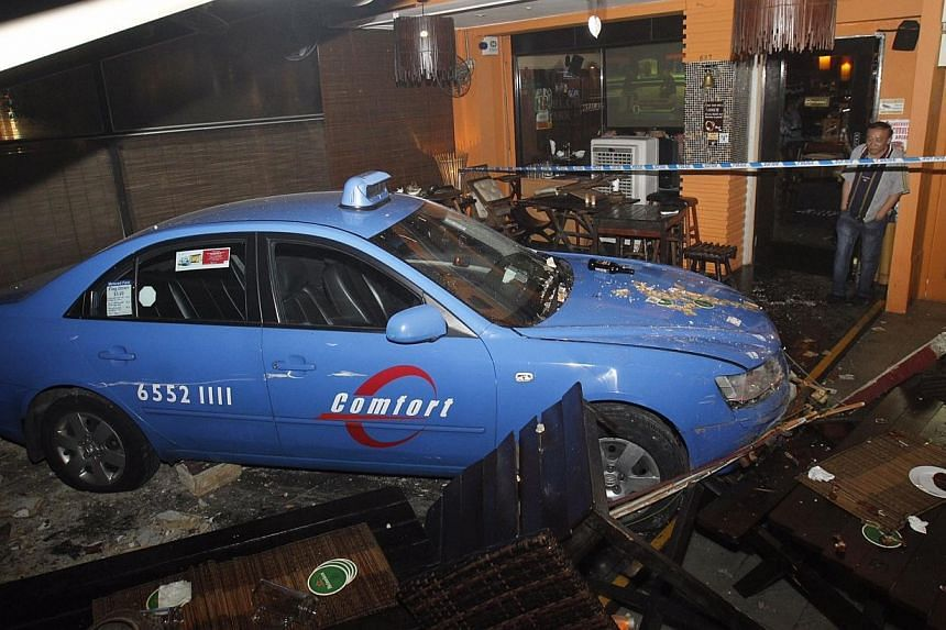 Five people were taken to hospital after a taxi, which had been involved in a road accident moments before, crashed into an outdoor sitting area of a bar along East Coast Road on Thursday night. -- ST PHOTO: KEVIN LIM