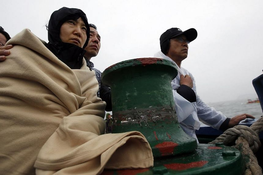 Family members of missing passengers who were on the South Korean Sewol ferry, which has sunk, watch the site of the accident from a ship in the sea off Jindo on April 17, 2014. Amid screams and shouts for help and the fear of death in the
