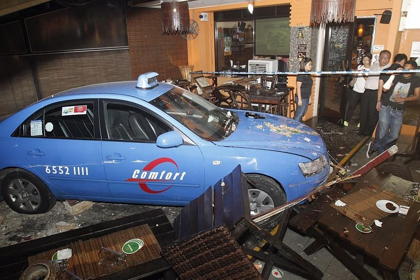 Five people were taken to hospital after a taxi, which had been involved in a road accident moments before, crashed into an outdoor sitting area of a bar along East Coast Road on Thursday night.-- ST PHOTO: KEVIN LIM