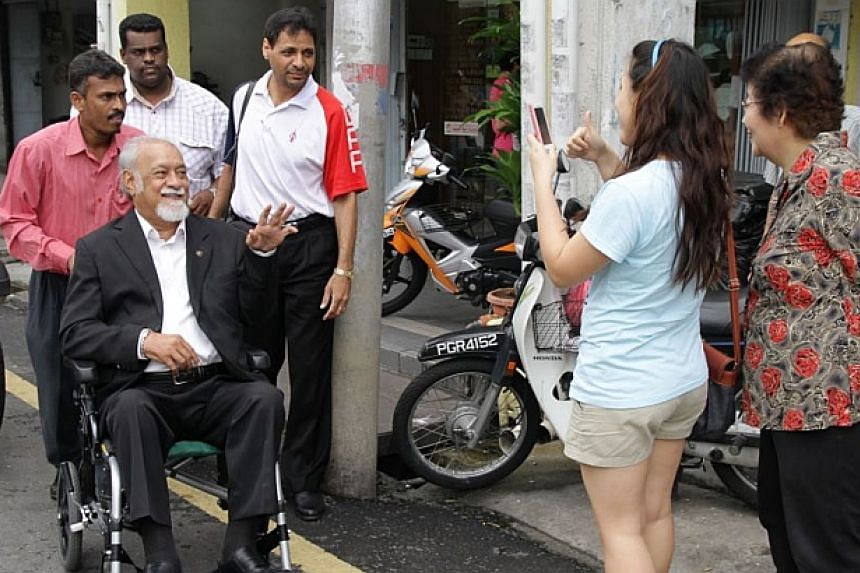 A photo showing Michael Cornelius pushing DAP chairman Karpal Singh on his wheelchair gesturing to the public while on his way to the press conference in Air Itam on 12 Nov 2011.-- FILE PHOTO: THE STAR/ ASIA NEWS NETWORK
