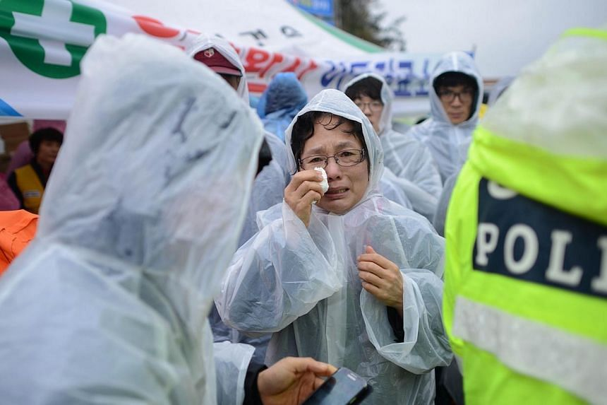 A relative (centre) reacts as she waits in a makeshift tent along a dockside in Jindo on Thursday, April 17, 2014, as the frantic search for nearly 300 people, most of them schoolchildren, missing after a South Korean ferry capsized extended into a s