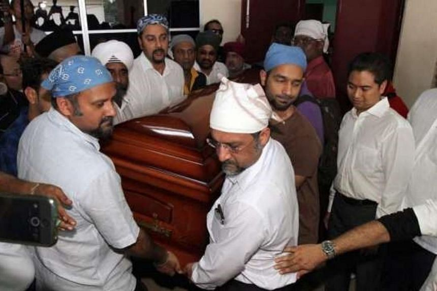 Karpal Singh's sons carry his coffin into the car that will send his remains back to his hometown, Penang, for the funeral.-- PHOTO: THE STAR/ ASIA NEWS NETWORK