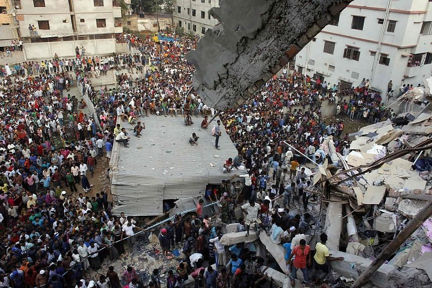 Rescue workers try to rescue trapped garment workers in the Rana Plaza building which collapsed, in Savar, outside Dhaka, on April 24, 2013.The Bangladesh government has seized properties belonging to the owner of a building that collapsed and