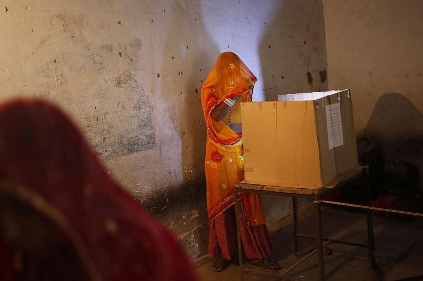 A woman casts her vote at a polling station in Ajmer district in the desert Indian state of Rajasthan on April 17, 2014.Voters in a parliamentary constituency in western India could be forgiven for asking the real candidates to please stand up.