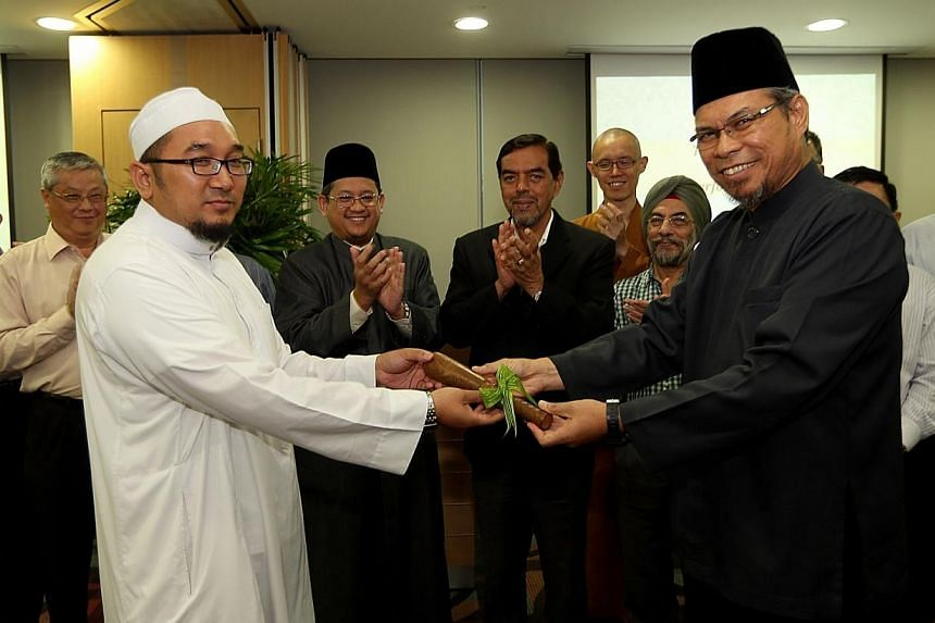 Ustaz Mohamed Ali Atan (front, right) hands over the leadership of the Harmony Centre to Ustaz Muhammad Fazalee Ja'afar (front, left), in the presence of Mufti Fatris Bakaram (fourth from left), Muis CEO Abdul Razak Maricar (fifth from left) and in