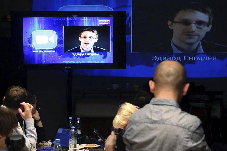 Journalists listen to a speech and a question posed by former US spy agency NSA contractor Edward Snowden, at a media centre during Russian President Vladimir Putin's live broadcast nationwide phone-in, in Moscow on Thursday, April 17, 2014. Snowden