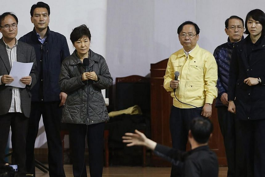 South Korean President Park Geun Hye (third from left) listens to the family member of a missing passenger who was on South Korean ferry Sewol, which sank at the sea off Jindo, during her visit to a gym where family members gathered, in Jindo on Thur