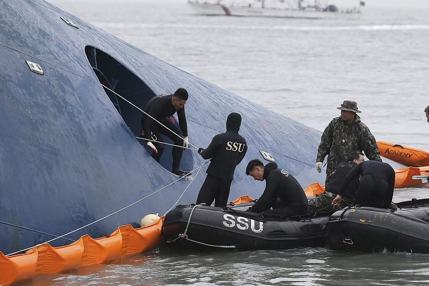 "Members of South Korean Ship Salvage Unit (SSU) search for passengers who were on the South Korea ferry ""Sewol"" which sank in the sea off Jindo on April 17, 2014. -- PHOTO: REUTERS"