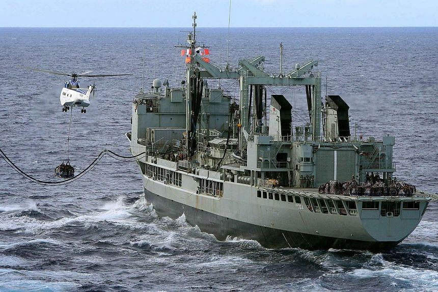 A USNS Cesar Chavez's helicopter, a Super Puma, carries supplies next to ships Australian Navy ships HMAS Success as they conduct a Replenishment at Sea with United States Navy Ship (USNS) Cesar Chavez (not pictured) in the southern Indian Ocean as t