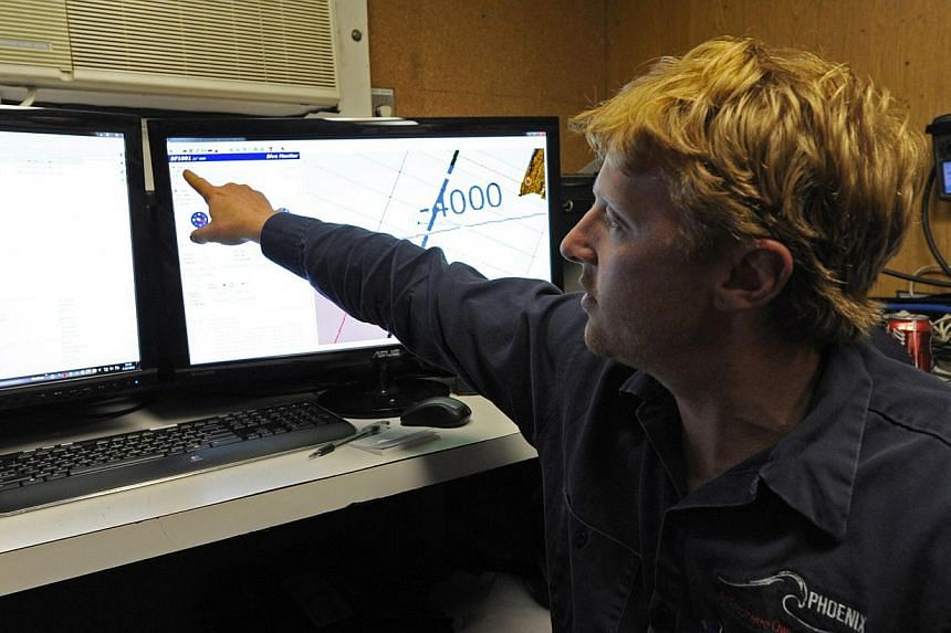 Mr Craig Turner from Phoenix International monitors the Artemis' depth and speed as the Autonomous Underwater Vehicle scans the ocean floor for missing Malaysia Airlines flight MH 370 in the southern Indian Ocean on April 16, 2014. -- FILE PHOTO: AFP