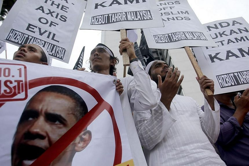 Supporters of the Hizbut Tahrir non-governmental organisation (NGO) pray while holding up placards against US President Barack Obama's planned visit to Malaysia next week, during a protest outside the US embassy in Kuala Lumpur on April 18, 2014. --