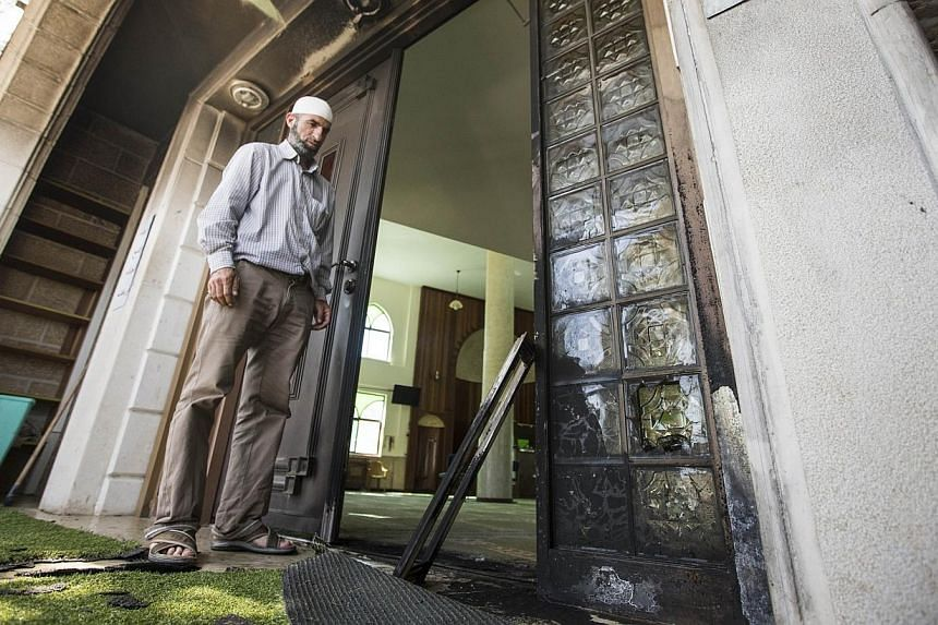 An Arab Israeli man stands at the entrance of a mosque in the northern Israeli city of Umm al-Faham on April 18, 2014, after vandals left anti-Arab graffiti overnight and damaged a door of the building.-- PHOTO: AFP