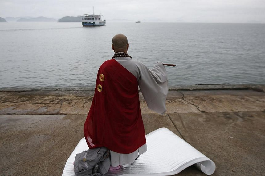 "A Buddhist monk prays for the missing passengers who were on the South Korean ferry ""Sewol"", which sank in the sea off Jindo, at a port where family members of the missing have gathered, in Jindo April 18, 2014. Night and day merged into each other o"