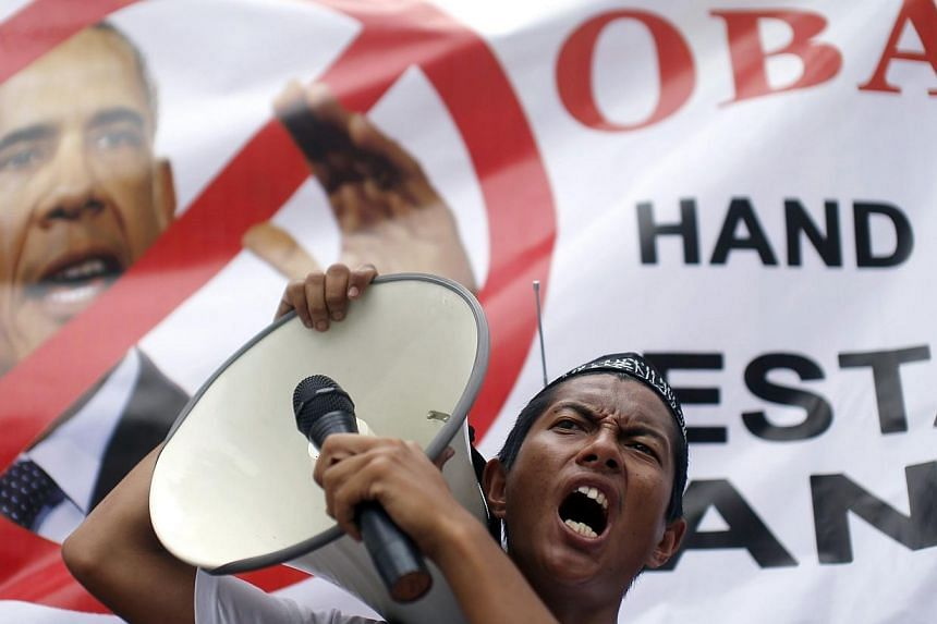 A supporter of the Hizbut Tahrir non-governmental organisation (NGO) holds a microphone to a loud-hailer as he shouts slogans against US President Barack Obama's planned visit to Malaysia next week, outside the US embassy in Kuala Lumpur on April 18,