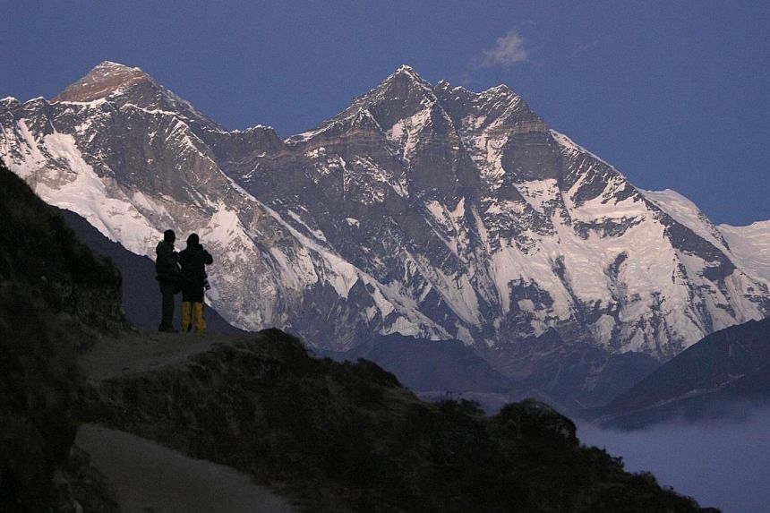 Travellers enjoy a view of Mount Everest at Syangboche in Nepal on Dec 3, 2009.The death toll from an avalanche that struck a party of Nepalese climbing guides on Friday morning on Mount Everest has risen to nine, a senior government official t
