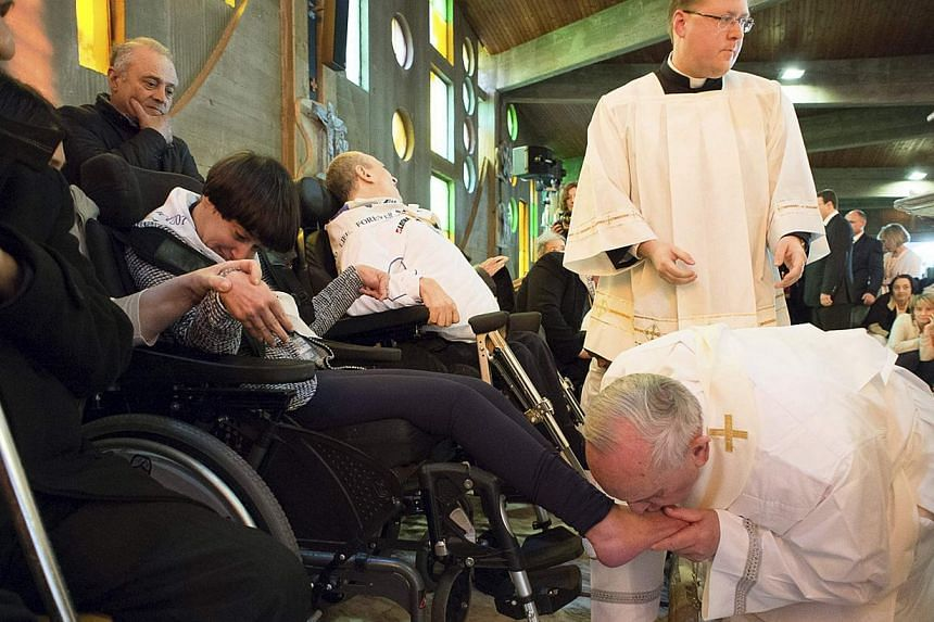 Pope Francis kisses the foot of a disabled person at the S. Maria della Provvidenza church in Rome, during Holy Thursday celebration, on April 17, 2014. Pope Francis visited a rehabilitation centre at the church for a service in which he washed and k