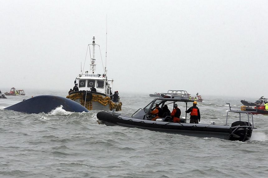 """South Korean rescue workers on a boat inject oxygen into the capsized passenger ship """"Sewol"""" which sank in the sea off Jindo, during a rescue operation April 18, 2014. A team of eight divers had entered a capsized South Korean ferry on Friday, April"""