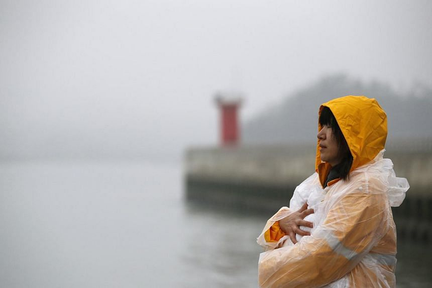 A family member of a passenger onboard the capsized South Korean ferry Sewol closes her eyes at a port where family members gathered to wait for news from the rescue team in Jindo on April 18, 2014. Rescuers struggled with strong waves and murky wate