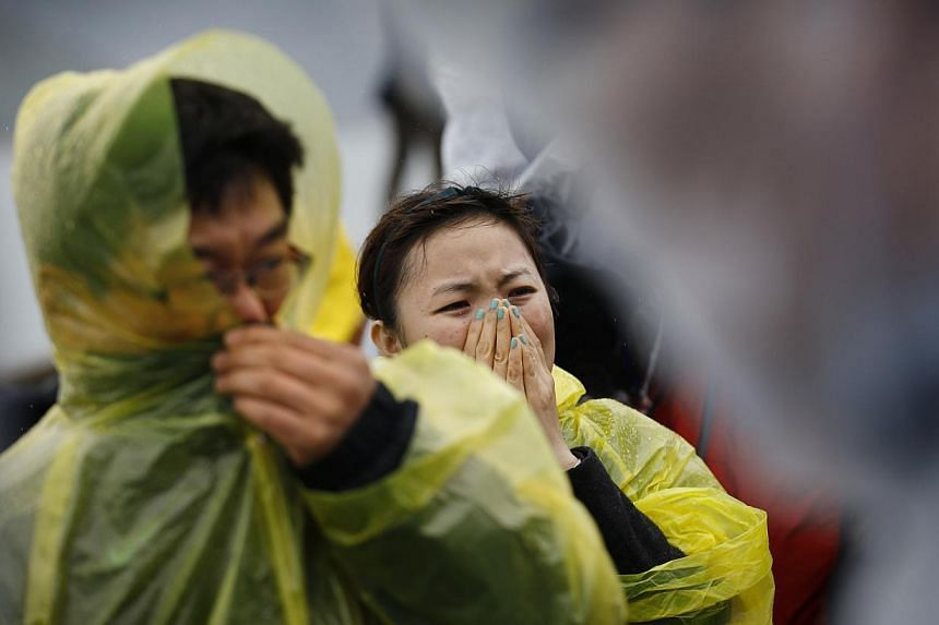 Family members of passengers missing on the overturned South Korean ferry Sewol, react at the port in Jindo on April 17, 2014. Police said late on Thursday that all messages claiming to have been sent from the sunken ferry Sewol after it went down at