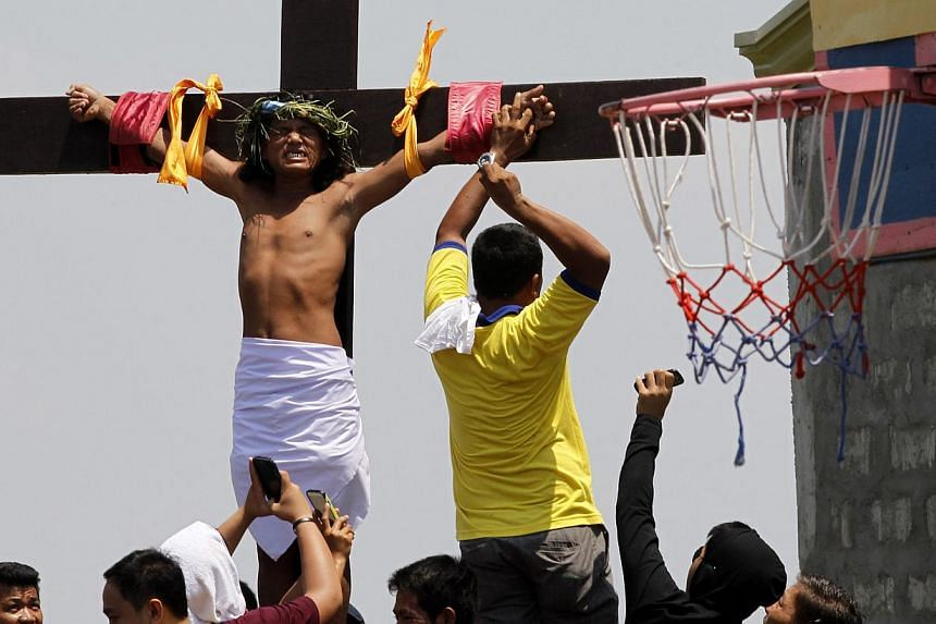 Ernesto Palmar, 40, reacts after a nail is pulled from his palm during a crucifixion to mark the death of Jesus Christ on Good Friday in San Matias town, Pampanga province, north of Manila, on April 18, 2014.Nearly 20 Filipinos and a Danish fil