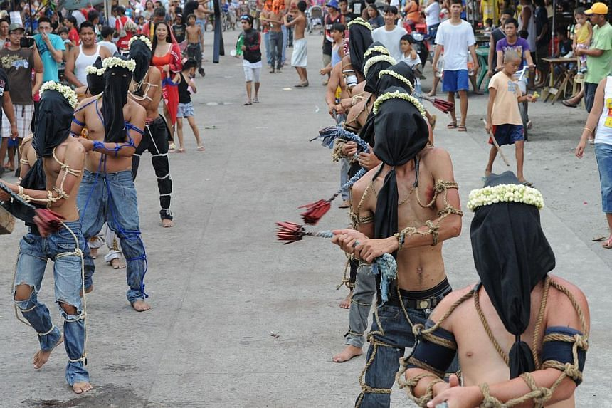 Penitents flagellate themselves as part of Lenten observance in Angeles City, Pampanga province, north of Manila, on April 17, 2014. -- PHOTO: AFP
