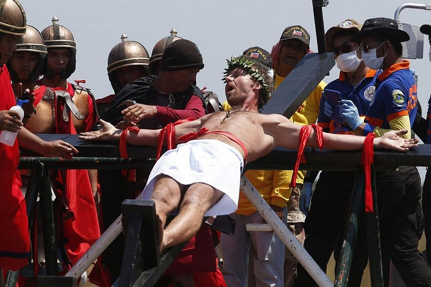 Danish film-maker Lasse Spang Olsen is nailed on a wooden cross as he takes part in a Good Friday ritual of the reenactment of the death of Jesus Christ in San Fernando, Pampanga in northern Philippines, on April 18, 2014. -- PHOTO: REUTERS