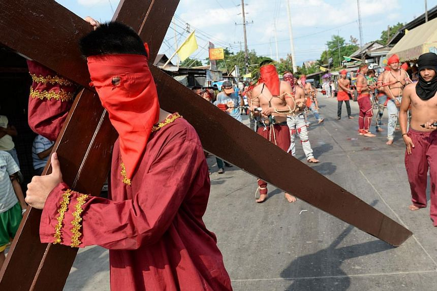 Penitents flagellate themselves while another carries a wooden cross as part of Lenten observance in Angeles City, Pampanga province, north of Manila, on April 17, 2014. -- PHOTO: AFP