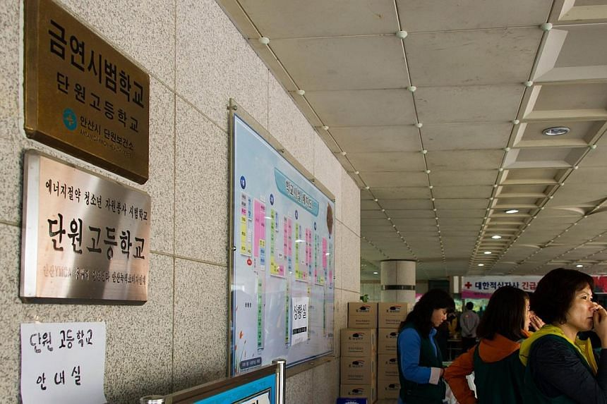 Volunteers stand and wait in a designated support area at Danwon High School in Ansan on Friday, April 18, 2014, as a rescue operation continues for passengers, which include students from the school after a South Korea ferry capsized on April 16.&nb