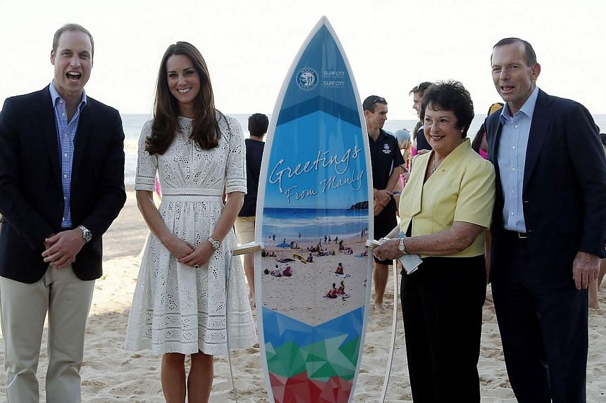 Catherine (second left), the Duchess of Cambridge, and her husband Britain's Prince William (left) pose for a photograph with Australian Prime Minister Tony Abbott (right) and Manly Lord Mayor Jean Hay standing next to a surfboard that the local coun
