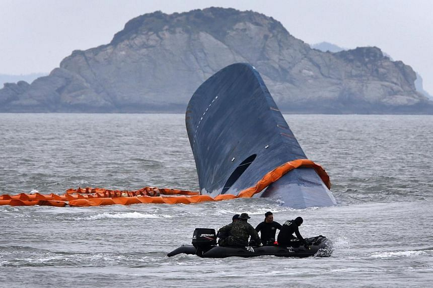 "A vessel involved in salvage operations passes near the upturned South Korean ferry ""Sewol"" in the sea off Jindo on April 17, 2014. Divers battled strong currents and murky waters on Friday, April 18, 2014, to finally enter a South Korean ferry"