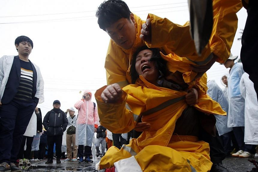 A family member (centre) of missing passengers who were on the South Korean ferry Sewol, which sank in the sea off Jindo, cries at a port where family members of missing passengers gathered in Jindo on April 18, 2014. -- PHOTO: REUTERS