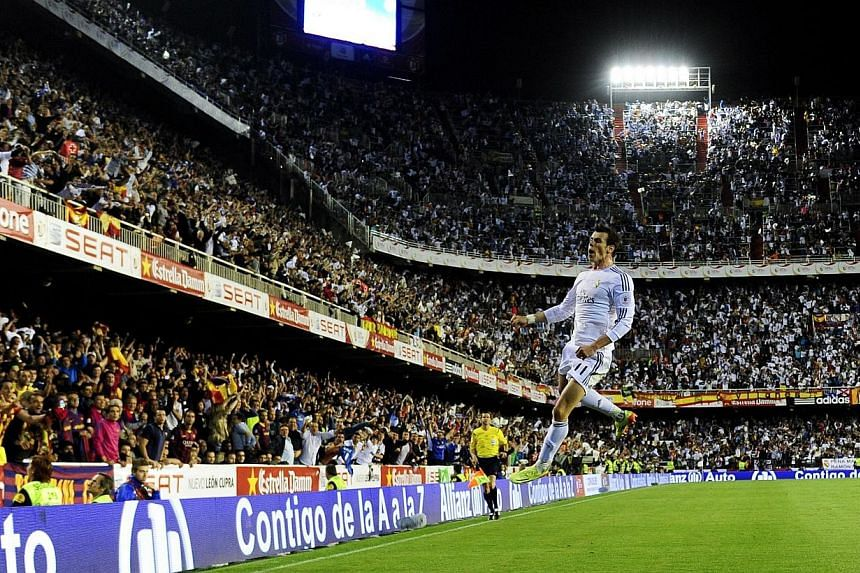 """Real Madrid's Welsh forward Gareth Bale celebrates after scoring during the Spanish Copa del Rey (King's Cup) final """"Clasico"""" football match FC Barcelona v Real Madrid CF at the Mestalla stadium in Valencia on Wednesday, April 16, 2014.Olympic"""