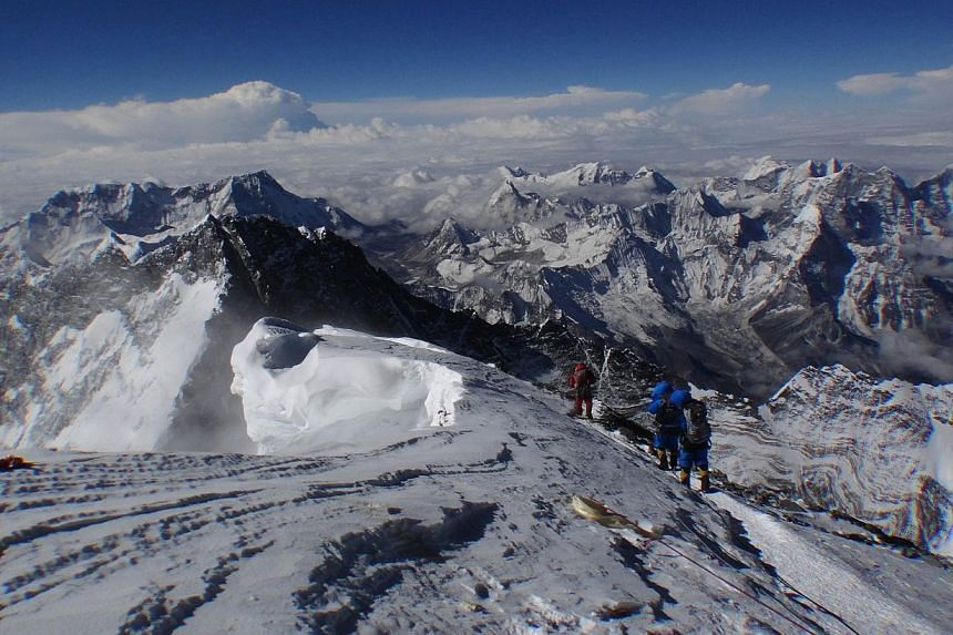 In this photograph taken on May 23, 2013, unidentified mountaineers look out from the summit of Mount Everest.At least six Nepalese climbing guides have been killed and six others are missing after an avalanche struck Mount Everest on Friday, A