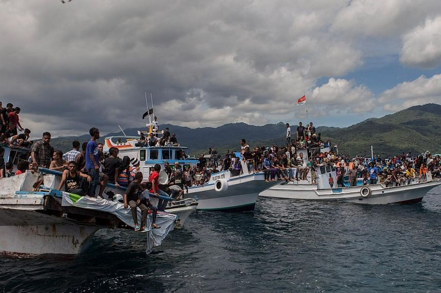 Boats overloaded with Christian devotees participate in a boat procession in the waters of Larantuka, East Nusa Tenggara province, eastern indonesian island of Flores on Friday, April 18, 2014. Seven people died, including three children, when a
