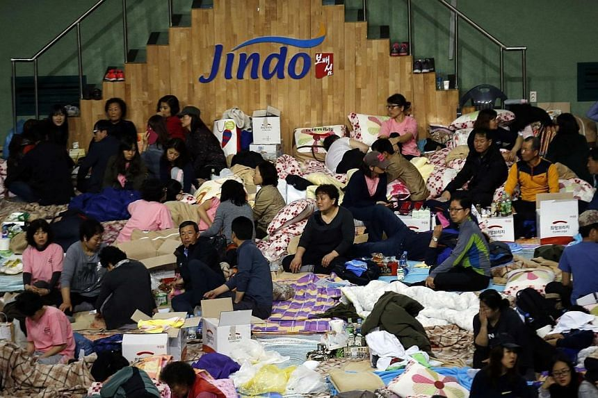 """Family members of missing passengers who were on South Korean ferry """"Sewol"""" which sank in the sea off Jindo wait for news from a rescue team, at a gym in Jindo on Friday, April 18, 2014.The families of the victims who lost their lives or went m"""