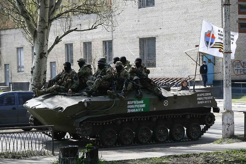 Armed men, wearing black and orange ribbons of St. George - a symbol widely associated with pro-Russian protests in Ukraine, drive an armoured personnel carrier in Slaviansk on April 18, 2014. -- PHOTO: REUTERS
