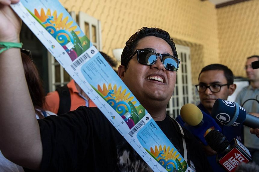 Football fan Vanderson Balbino shows the eight tickets he bought for the upcoming Fifa World Cup Brazil 2014 as the designated ticketing pick-up centres opened in 12 host cities on April 18, 2014, at Botafogo's club in Rio de Janeiro, Brazil. -- PHOT