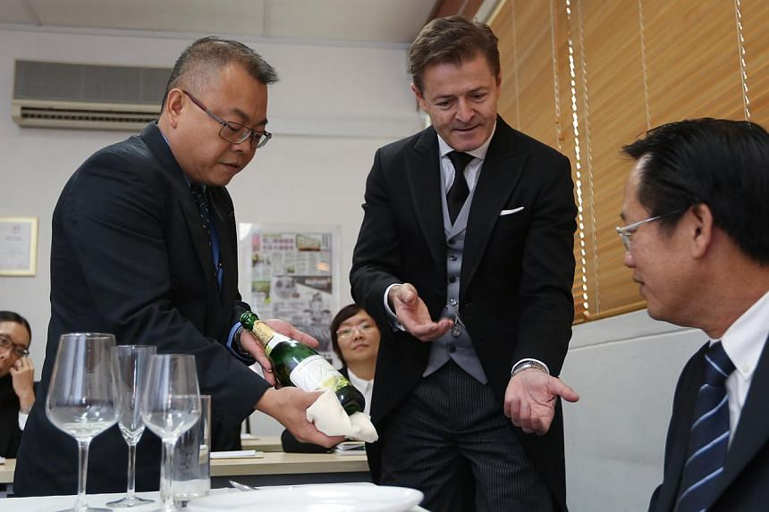 Mr Gary Williams of the British Butler Institute, who is in Singapore for a week, demonstrating how to serve champagne to Mr Simon Ho (left), one of the six who will help train domestic helpers. Nation Employment plans to hold classes in June and hav